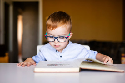 Cute toddler boy with down syndrome with big glasses reading intesting book.