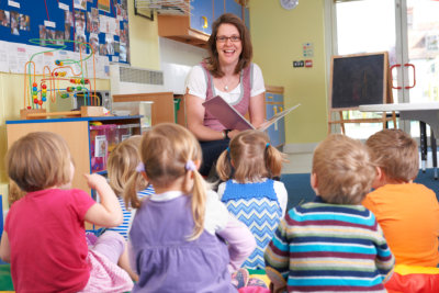 Pre School Children Listening To Teacher Reading Story