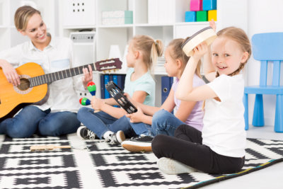 Shot of primary class students and a teacher playing different instruments